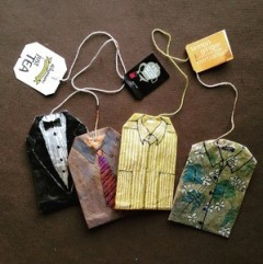 four teabags painted to look like folded men's shirts